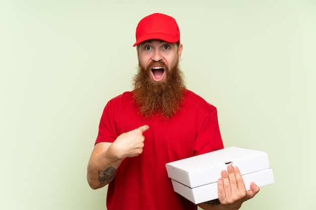 Delivery man with long beard over isolated green wall with surprise facial expression