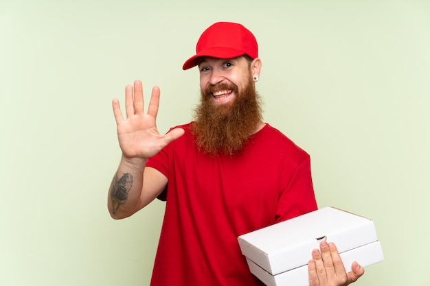 Delivery man with long beard saluting with hand with happy expression