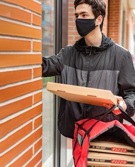 택배를 위해 빨간 가방을 들고 문지기를 부르는 그의 얼굴에 마스크가있는 배달 남자