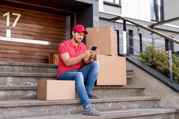 Uomo di consegna con cellulare