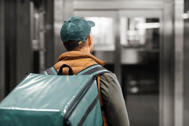 Uomo di consegna con pacchetto in ascensore