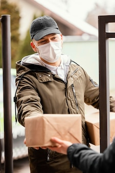 Uomo di consegna con il pacchetto che indossa la maschera