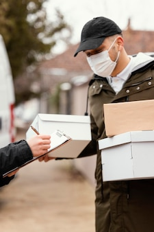 Delivery man with package wearing mask