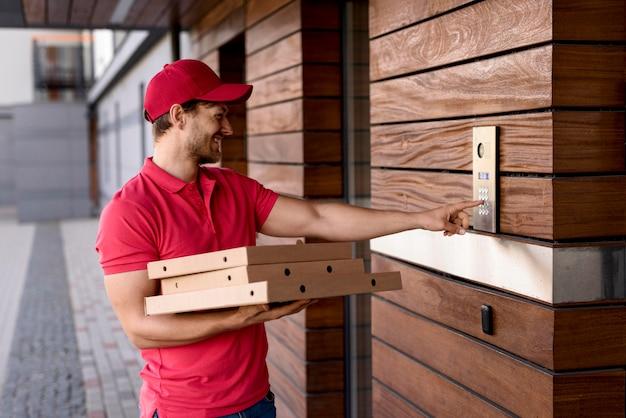 Uomo di consegna con pacchi alla porta