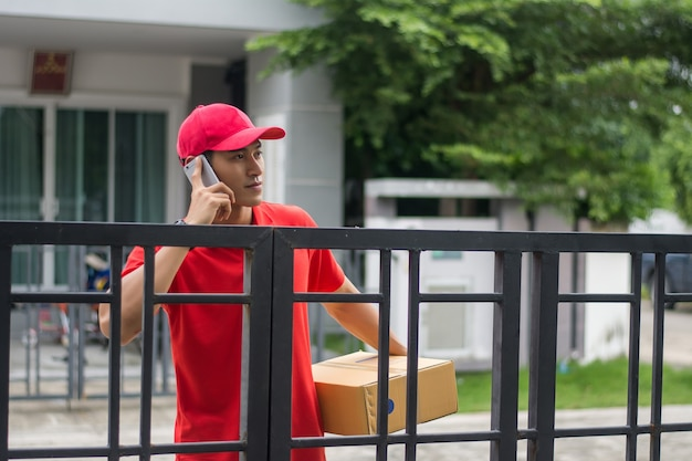 Delivery man with parcel calling a customer in front of home.