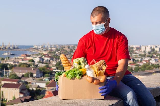 新鮮な食料品の箱を保持している保護マスクと手袋を持つ配達人