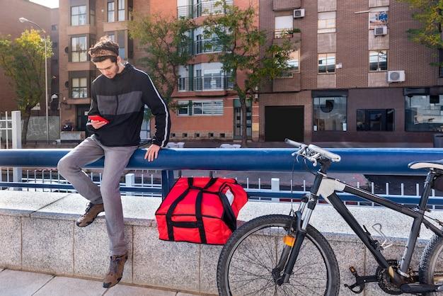 빨간 가방과 앉아있는 자전거를 가진 배달원, 그의 휴대 전화를 사용하여 자전거로 다음 주문을하십시오.
