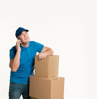 Delivery man with smartphone and cardboard boxes