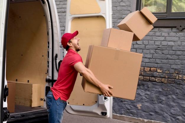 Uomo di consegna con pila di pacchi