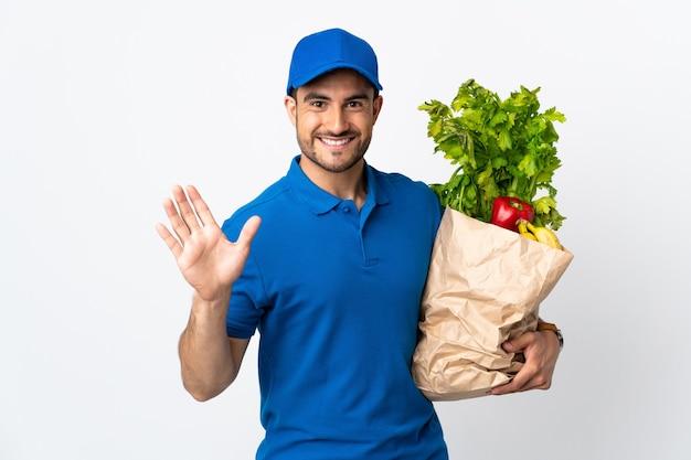 Доставщик с овощами, изолированные на белой стене, салютуя рукой с счастливым выражением лица