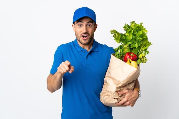 Доставщик с овощами, изолированными на белой стене, удивился и указал на фронт