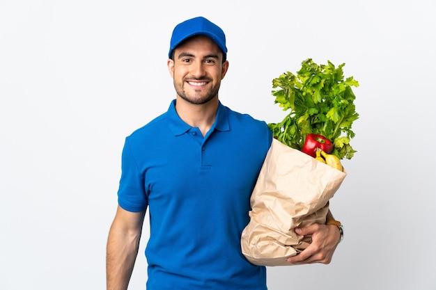 Экспедитор с овощами, изолированными на белой стене с счастливым выражением лица