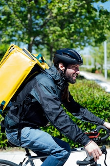 Delivery man with yellow backpack riding a bicycle
