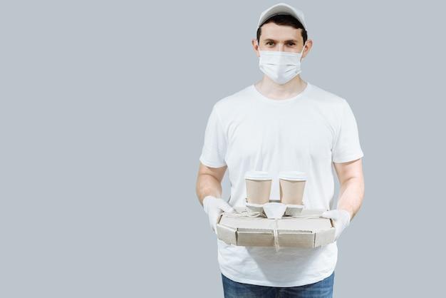 Работник доставки в белой кепке, футболке, униформе, маске, перчатках, заказывает еду, коробки для пиццы и кофе
