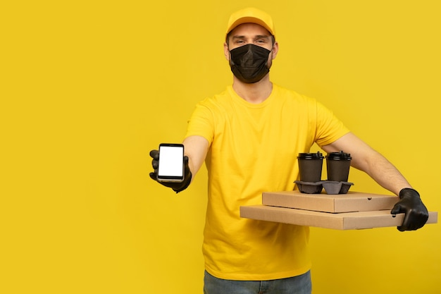 Delivery man in yellow cap, tshirt uniform, mask, gloves isolated. guy hold takeaway cup of coffee