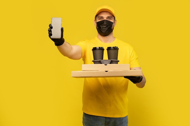 Delivery man in yellow cap, tshirt uniform, mask, gloves isolated on yellow. guy hold takeaway cup of coffee