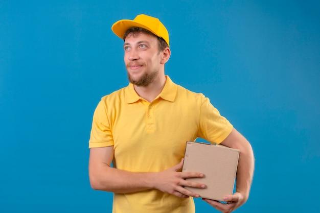 Fattorino in maglietta polo gialla e berretto che tiene il pacchetto della scatola nelle mani sorridente amichevole alzando lo sguardo in piedi sul blu