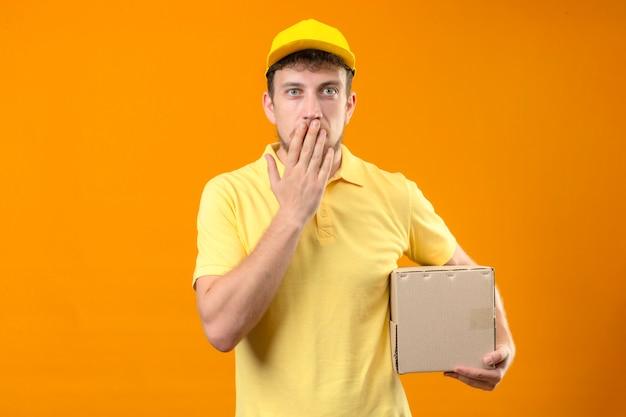 Fattorino in maglietta polo gialla e berretto tenendo il pacchetto scatola scioccato coning bocca con la mano in piedi sul arancione isolato