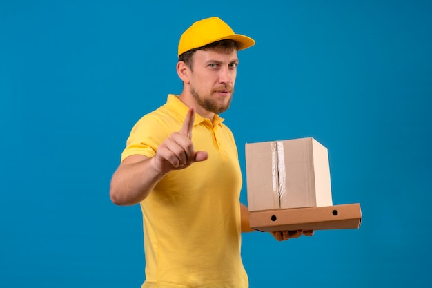 Delivery man in yellow polo shirt and cap holding cardboard boxes and pointing to camera with finger with frowning face standing on blue