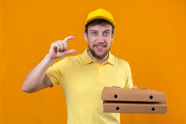 Fattorino in maglietta polo gialla e cappuccio tenendo scatole per pizza gesticolando con le mani che mostrano il simbolo di misura segno di piccole dimensioni su arancione isolato