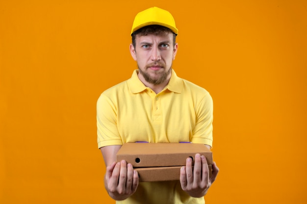 Delivery man in yellow polo shirt and cap holding pizza boxes looking at camera with angry expression standing on orange