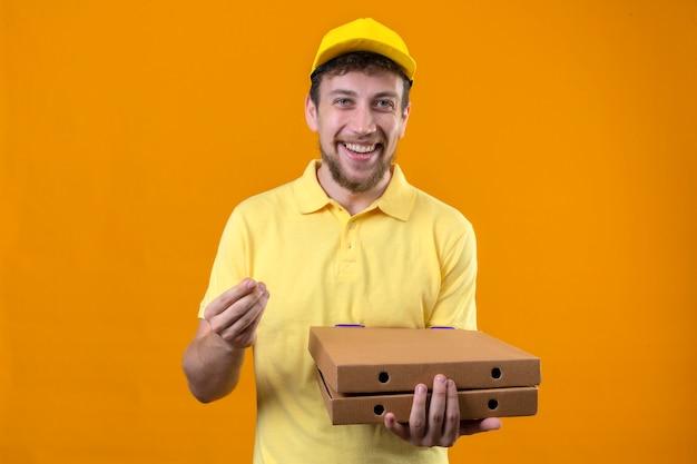 Fattorino in maglietta polo gialla e berretto in possesso di scatole per pizza guardando la fotocamera con il sorriso sul viso facendo gesto di denaro con la mano in piedi sull'arancio