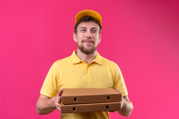 Delivery man in yellow polo shirt and cap holding pizza boxes looking confident and proud smiling cheerful standing on isolated pink