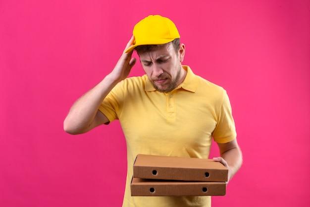 Uomo di consegna in maglietta polo gialla e cappuccio tenendo scatole per pizza in piedi con con la mano sulla testa per errore ricordare l'errore dimenticato il concetto di cattiva memoria sul rosa isolato