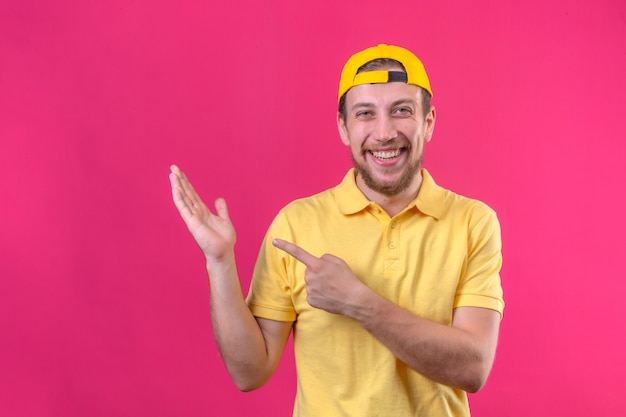 Delivery man in yellow polo shirt and cap smiling cheerfully pointing with hand and finger to the side on isolated pink