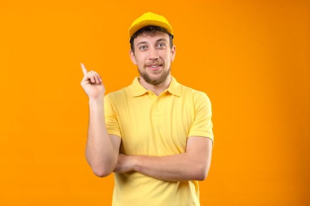Fattorino in maglietta polo gialla e cappello sorridendo felice puntando con la mano e il dito a lato in piedi su arancione isolato