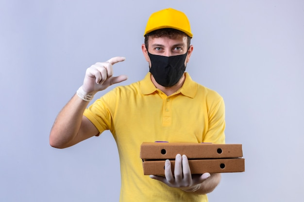 Uomo di consegna in maglietta polo gialla e berretto che indossa la maschera protettiva nera che tiene scatole per pizza gesticolando con le mani che mostrano il simbolo di misura del segno di piccole dimensioni su bianco isolato