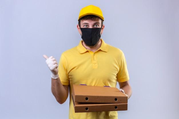Fattorino in maglietta polo gialla e berretto che indossa la maschera protettiva nera che tiene scatole per pizza guardando fiducioso mostrando pollice in alto in piedi sul bianco isolato