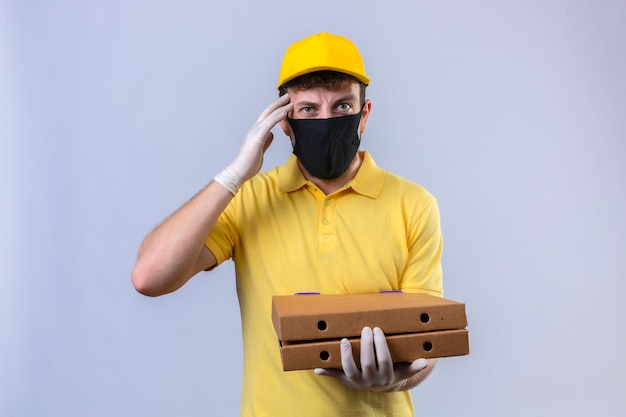 Fattorino in maglietta polo gialla e berretto che indossa una maschera protettiva nera che tiene scatole di pizza guardando malato stanco e onworked toccando la testa avendo mal di testa in piedi sul bianco isolato