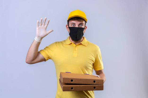 Fattorino in maglietta polo gialla e berretto che indossa una maschera protettiva nera con scatole per pizza che mostrano il numero cinque con la mano che sembra sorpreso in piedi su bianco