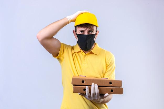 Fattorino in maglietta polo gialla e berretto che indossa una maschera protettiva nera che tiene scatole per pizza sorpreso con la mano sulla testa per errore ricorda l'errore dimenticato il concetto di cattiva memoria su isolato