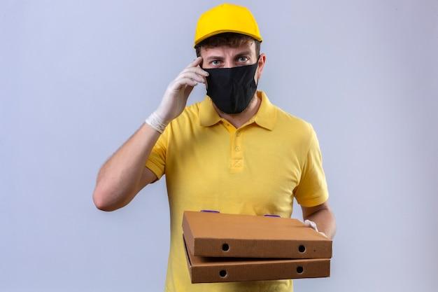 Uomo di consegna in maglietta polo gialla e cappuccio che indossa la maschera protettiva nera tenendo scatole per pizza toccando la sua testa cercando di ricordare cosa importante pensare in piedi su backg bianco isolato