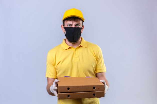 Delivery man in yellow polo shirt and cap wearing black protective mask holding pizza boxes with angry expression standing on white