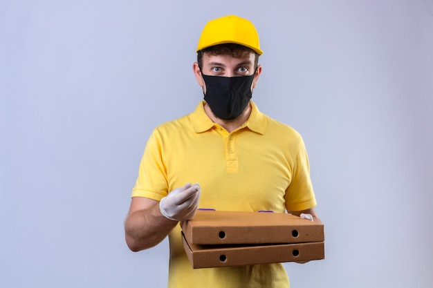 Delivery man in yellow polo shirt and cap wearing black protective mask with smile on face making money gesture with hand standing on white
