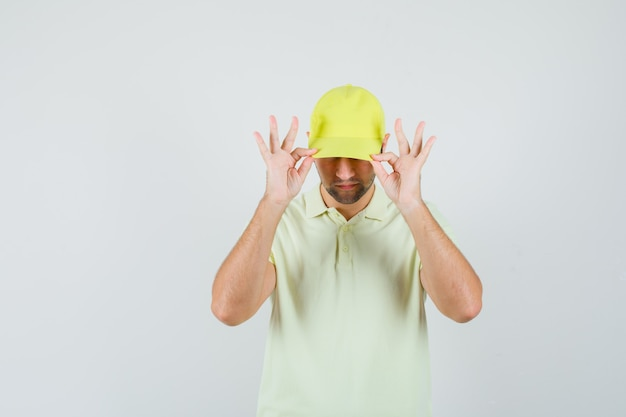 Fattorino in uniforme gialla che tira giù il berretto sugli occhi e sembra elegante, vista frontale.
