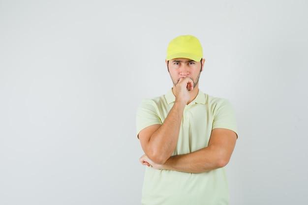 Fattorino in uniforme gialla in piedi nella posa di pensiero e guardando esitante, vista frontale.