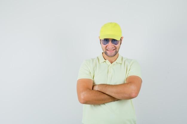 Fattorino in uniforme gialla in piedi con le braccia incrociate e guardando fiducioso, vista frontale.