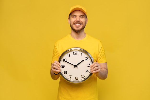 Delivery man in yellow workwear hold clock isolated on yellow wall studio portrait