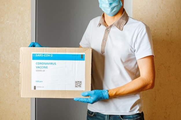 Delivery medical box of vaccines. the courier delivers the vaccine. covid 19 virus