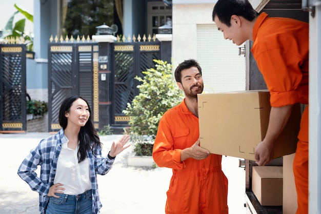 Delivery men unloading box for customer