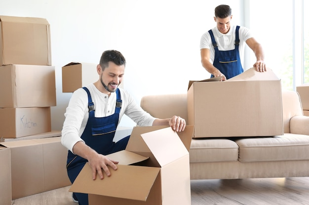 Delivery men with moving boxes in room at new home