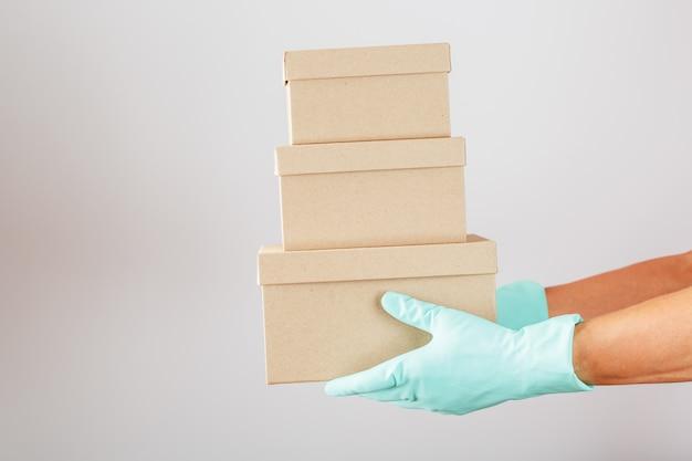 白い背景の上のウイルスや病気に対する保護のための手袋と小包の配達。