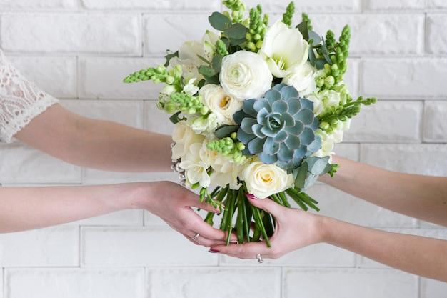手から手への花束の配達。ビジネス-顧客のために注文する植物相組成物を作る。現代の結婚式の組み立てで白いバラと多肉植物