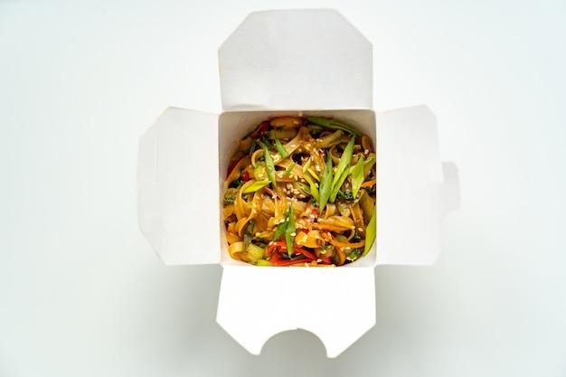 Доставка готовых блюд азиатской кухни. лапша с овощами и морепродуктами в белой коробке. вкусный ужин. заказывать еду по телефону или онлайн. палочки для суши.