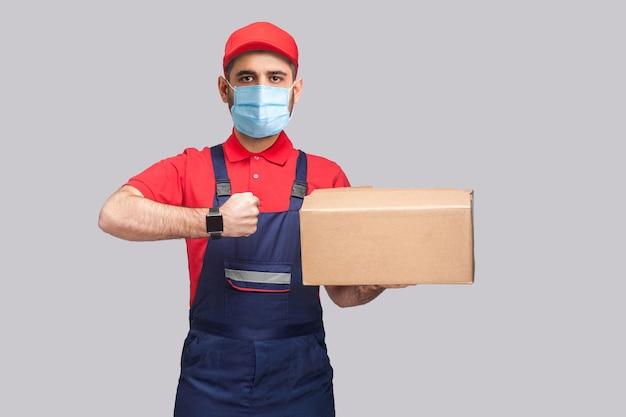 検疫での配達。オンタイムサービス!青いユニフォームと赤いtシャツを着た外科用医療マスクを持った男性が立って、配達ボックスを持って、灰色の背景に時計を見せています。屋内ショット、孤立、