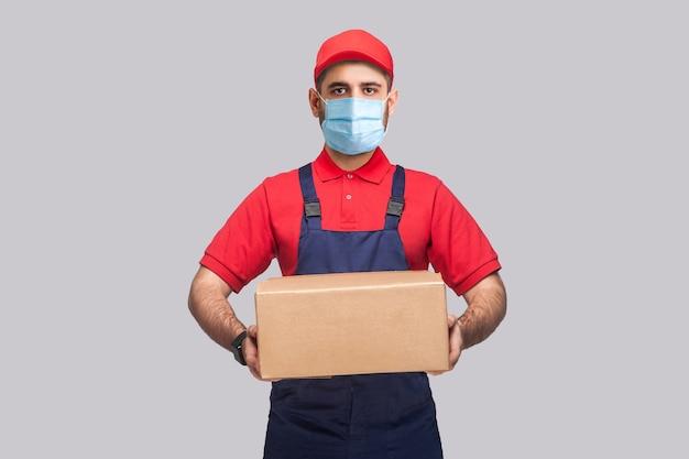 検疫での配達。青い制服を着た外科用医療マスクと灰色の背景に段ボール箱を立って保持している赤いtシャツを着た若い男の肖像。屋内、スタジオショット、孤立、